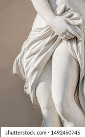 Statue of ancient sensual half naked Renaissance Era woman with long baked legs in Potsdam at smooth wall background, Germany, details, closeup