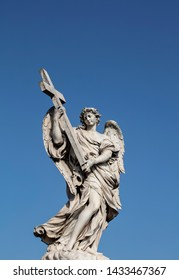 The statue of the Angel with the cross on the Ponte Sant'Angelo. The baroque statue can be seen against a deep blue summer sky and is a perfect example of baroque sculpture in Rome.