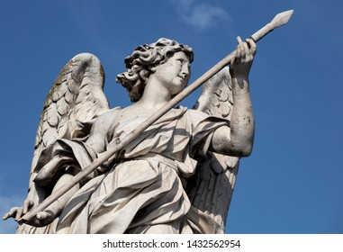 Statue of the Angel with the lance on the Ponte Sant'Angelo. The baroque statue can be seen against a deep blue summer sky and is a perfect example of baroque sculpture in Rome.