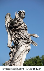 The statue of the Angel with the nails on the Ponte Sant'Angelo. The baroque statue can be seen against a deep blue summer sky and is a perfect example of baroque sculpture in Rome.