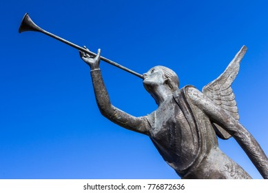 Statue of an angel playing a trumpet over blue sky