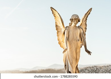 statue of angel with wings against light sky at cemetery. Closing stoned angel in an old cemetery.. Graveyard old weathered stone sad angel sculpture on funeral. copy space text.