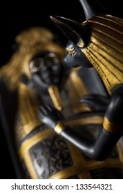 Statue of Anubis with the mummy of the deceased on a black background, selective focus