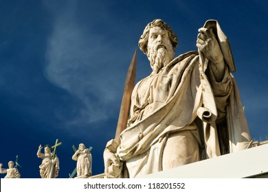 Statue of Apostle Paul in front of the St Peter's Basilica, Rome, Italy. Detail of the facade exterior on the blue sky background. Renaissance sculpture of the Apostle Paul with a sword in sunlight.