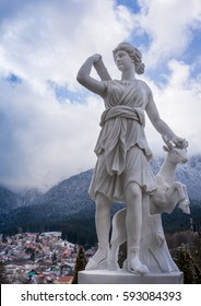 The statue of Artemis and a deer made from marble above a city. The hunter and the deer.