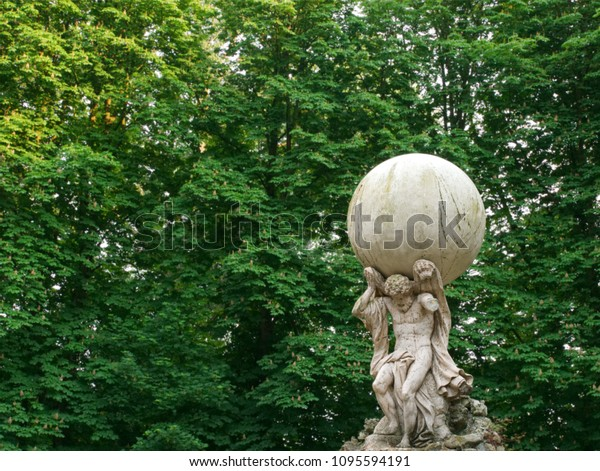 Statue of Atlas god carrying the world globe on its shoulders standing in the park with a green background of the leafs of the trees