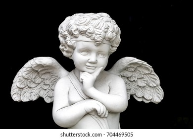 Statue of a baby angel in a park ,Cupid decoration in the garden.