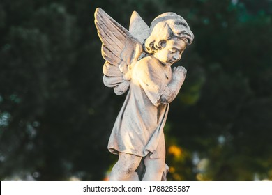 statue of baby angel with wings against green trees at cemetery. Closing stoned angel child praying in an old cemetery. Graveyard old crying angel sculpture on funeral. Death, loss, condolence concept