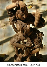 Statue - A beautiful wooden carving of a women of the Indian historical era who is depicting make-up holding mirror in one hand