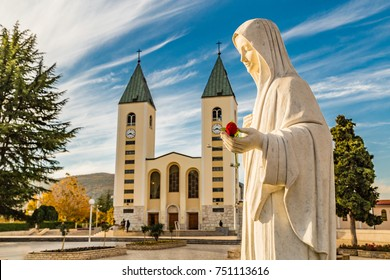 statue of the Blessed Virgin Mary holding a red rose while Saint James Church in Medjugorje is in background