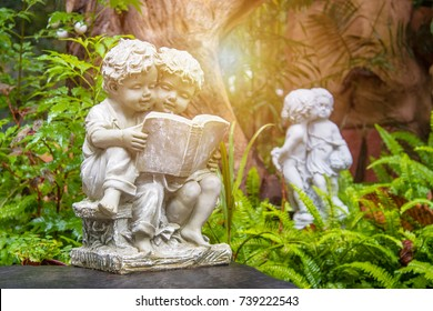 Statue of boy and girl reading the book in garden.