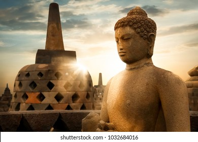 Statue of Buddha against the background of the sunrise with rays of light in the Borobudur Temple.  Java island. Indonesia. Famous historical place. Outside. Religion concept.
