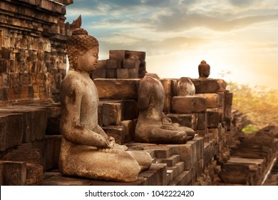 Statue of Buddha against the background of the sunrise in the temple of Borobudur.  Java island. Indonesia. Famous historical place. Outside.