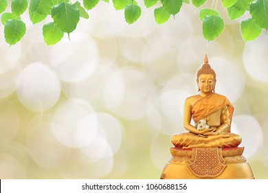 Statue Buddha and bodhi leaf on bokeh background, religion background, buddhism background.