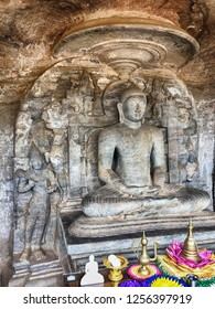 A statue of Buddha carved into a stone cliff sits in a Lotus pose in the Gal Vihare rock shrine in the ancient city of Polonnaruwa in Sri Lanka.