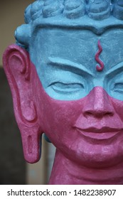 Statue of the Buddha close up. Pink Buddha's Face. The calm face of the Buddha in blue and pink color. Mediation face in mindfullness meditaiton.