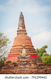 Statue of Buddha with golden fabric clothes sitting in front of old Stupa at Ayutthaya Thailand