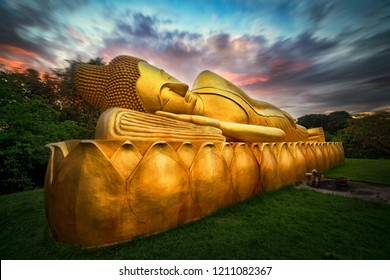 Statue of Buddha sleeping carved from  golden sandstone on green grass under the beautiful sky