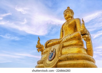 Statue of Buddha in Thailand on background sky with clouds