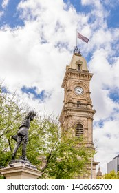 The statue of Captain Charles Sturt Explorer and the Victoria Tower of Adelaide against a beautiful blue sky with some clouds, Southern Australia