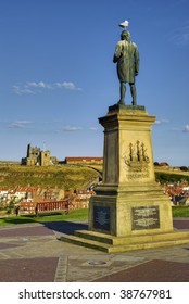 Statue of Captain James Cook with Whitby town ruined abbey in background, North Yorkshire, England.
