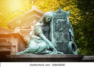 Statue in a cemetery of Paris at sunset