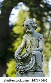 Statue of child with laurel wreath at a cemetery
