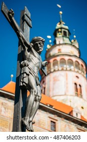 The Statue Of The Crucified Christ On The Cross On The Lazebnicky Most Bridge On A Background Of An Old Castle Tower In Cesky Krumlov, Czech Republic. The Christian Cross With Jesus