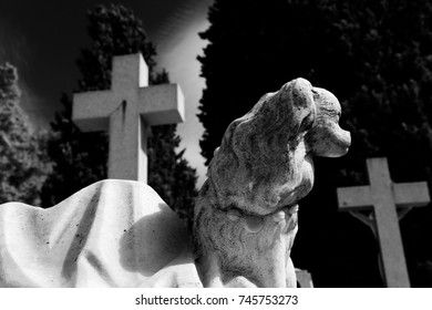 Statue of dog and cross in cemetery