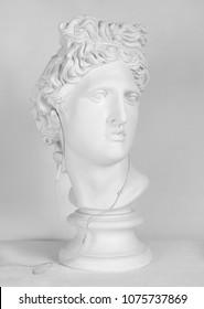 Statue. Earphone. Isolated. Gypsum statue of Apollo's head. Man. Plaster statue of Apollo's head in earphones.  Head.