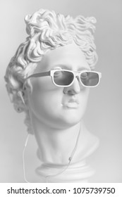 Statue. Earphone. Isolated.  Gypsum statue of Apollo's head. Man. Statue. Plaster statue of Apollo's head in earphones and white sunglasses. Head.