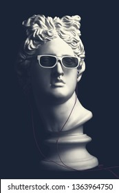 Statue. Earphone. Isolated. Gypsum statue of Apollo's head. Man. Creative. Plaster statue of Apollo's head in earphones and white sunglasses. Apollo Belvedere. Artwork