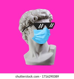 Statue. Earphone. Isolated. Gypsum statue of David's head. Man. Creative. Plaster statue of David's head in pixel glasses and medical mask. Minimal concept art.