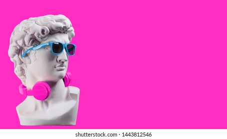Statue. Earphone on a pink background. Gypsum statue of David's head. Creative. Plaster statue of David's head in blue sunglasses. Minimal concept art.