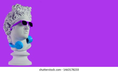 Statue. Earphone on a purple background. Gypsum statue of David's head. Creative. Plaster statue of Apollo's head in blue sunglasses. Minimal concept art.