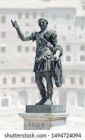 Statue of emperor Trajan in Rome, Italy. On background: a building of Trajan's Forum