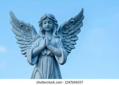 Statue of a fairy on a sky background
