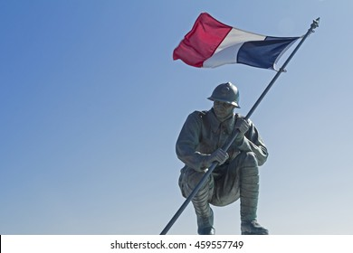 A statue of a French soldier, flying the French flag, in Saint Pierre Cemetery. Saint Pierre et Miquelon are two small French islands just south of Newfoundland, Canada.