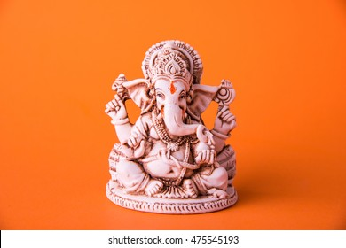 statue of Ganesha Idol made of white marbal on plain bright orange background. Clear space for text or headline