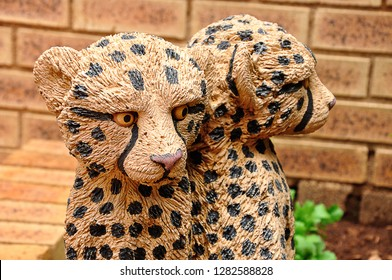 A statue in a garden of a baby leopard