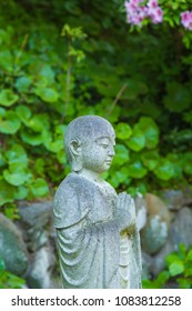 Statue in garden surrounded by green foliage.