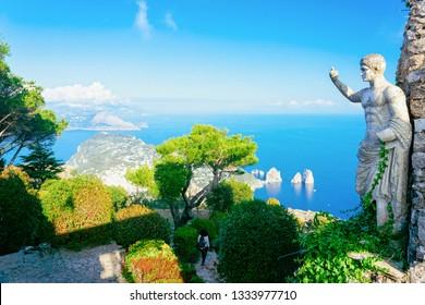 Statue and gardens at Capri Island town, Italy. Landscape with sculpture and Blue Mediterranean Sea, Italian coast. Anacapri in Europe. View on Faraglioni, summer. Amalfi scenery and Solaro mountain