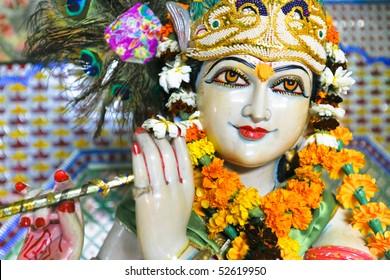 Statue of garlanded Hindu god Krishna playing flute in Delhi, India.