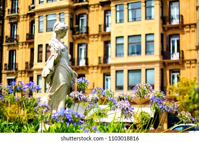 Statue of the girl with flowers on the foregorund and bright yellow building facade on the background in San Sebastian, Spain
