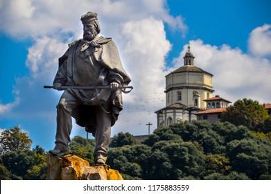 "A statue of Giuseppe Garibaldi, an Italian national hero involved in the Italian unification in the 1800s. The statue is placed in Turin, Italy. In the background, the ""monte dei cappuccini"" church."