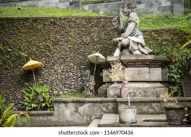 Statue of a god at the Balinese Hindu temple Tirta Empul, near Ubud, beautifully offset by umbrellas and geometric architectural stonework.