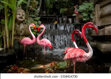Statue at the Golden Mountain in Bangkok. pink flamingos among green garden