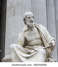 A statue of a Greek god sits deep in thought peers up from his readings.