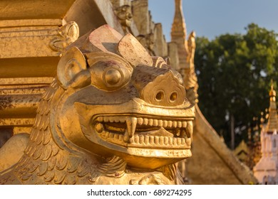 Statue of guardian lion chinthe in Shwezigon paya, Bagan, Myanmar. Chinthe are often installed at entrances to Buddhist temples in Asia. Closeup on head.