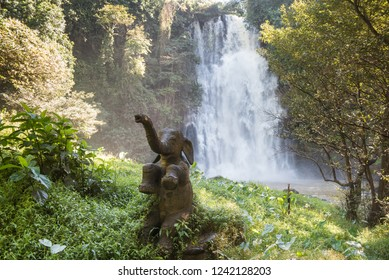 Statue of happy baby elephant with waterfall on the background